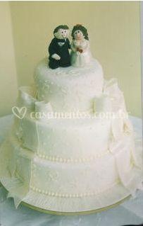 Bolo de casamento com noivinhos e laços