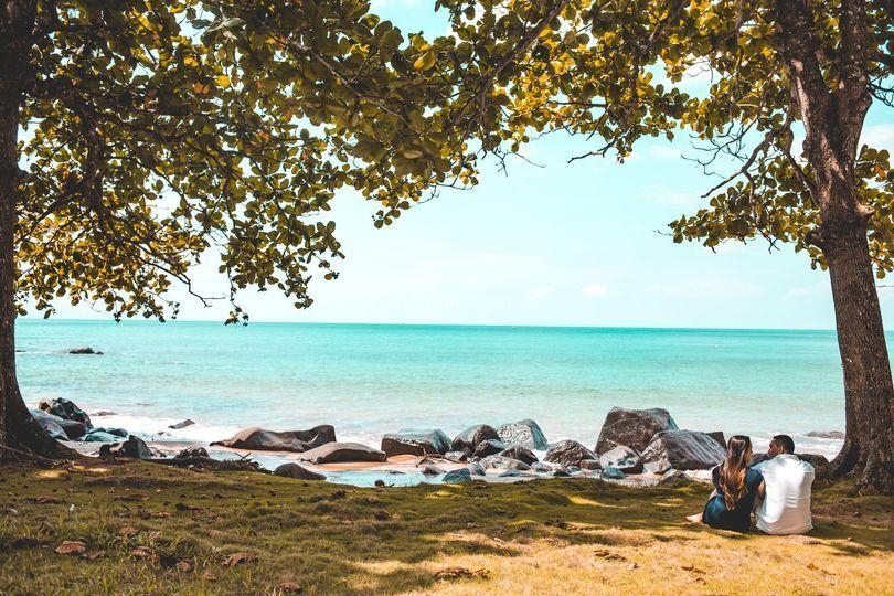 Casal sentado a beira da praia