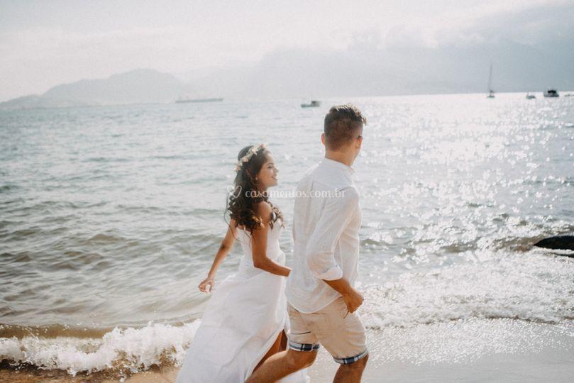 Noivos correndo na praia