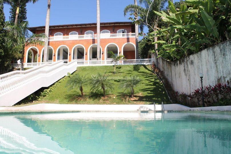 Vista da mansão pela piscina