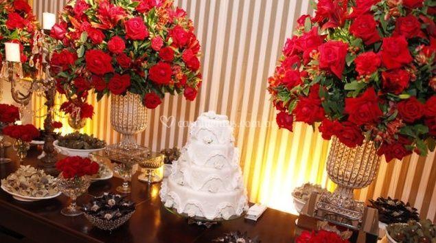 Bolo de casamento e flores vermelhas