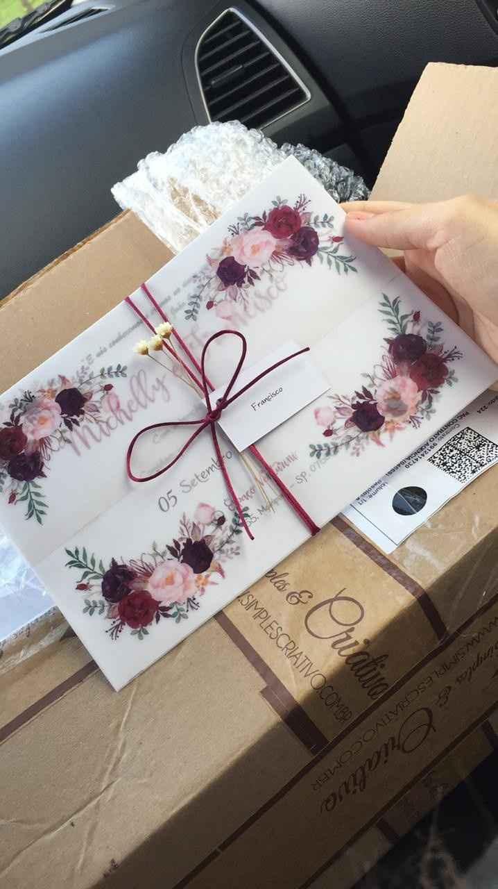 Esse é meu convite vem 3 raminhos de flores neles o papel é branco com a escrita marsala e o envelop