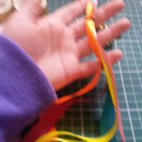 Junta uma fita de cada cor (acho que eram 6 cores) e dá um jeito de prender na ponta do palito. Eu a